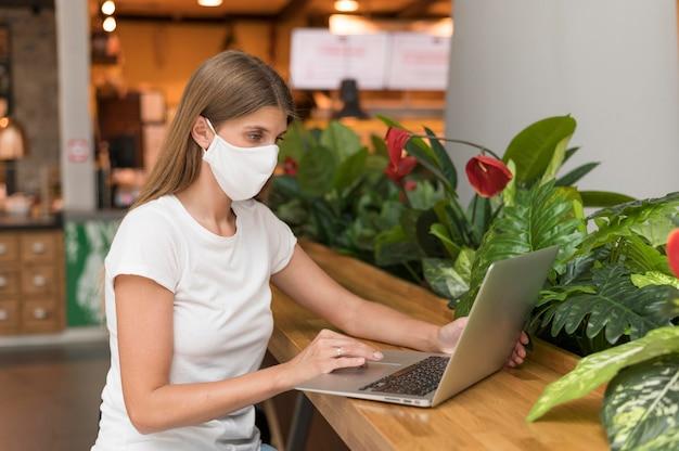 Frau, die am laptop mit maske arbeitet