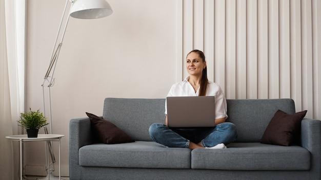 Frau, die am laptop von zu hause oder vom studenten arbeitet, der von zu hause oder vom freiberufler studiert. moderne geschäftsfrau in einem weißen hemd und in jeans.