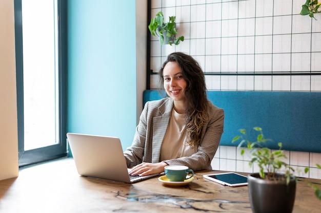 Frau, die am mittleren schuss des laptops arbeitet