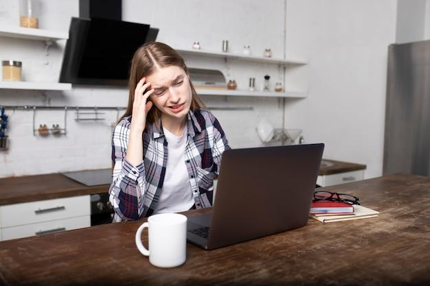 Frau, die am morgen zu hause arbeitet. ein junges mädchen hat kopfschmerzen. sie benutzt ihren laptop