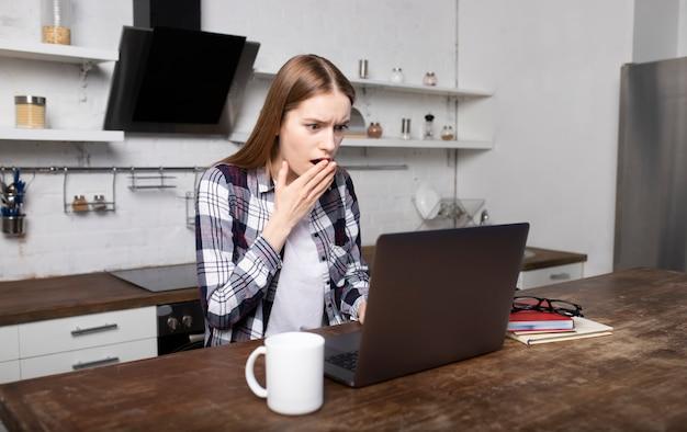 Frau, die am morgen zu hause arbeitet. mädchen, das kaffee trinkt. sie benutzt ihren laptop