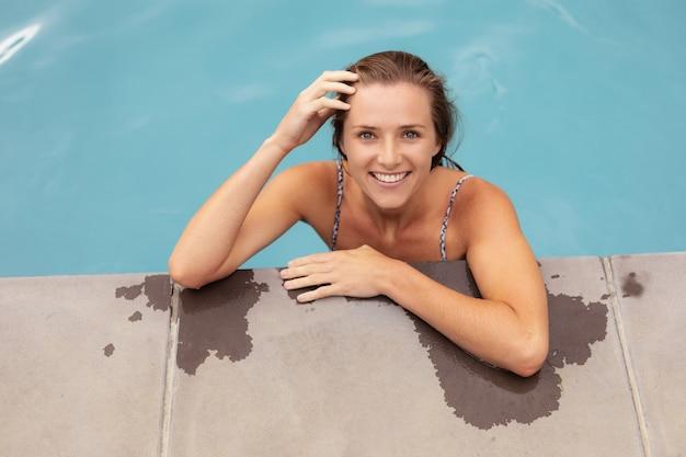 Frau, die am rand des swimmingpools steht