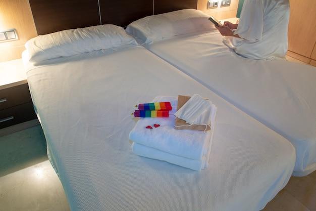 Frau, die am rand eines hotelbetts sitzt und das mobiltelefon konsultiert mit gefalteten handtüchern am fuß der maske mit einer schutzmaske und einem detail von zwei roten herzen und zwei schwulen flaggen textfreiraum