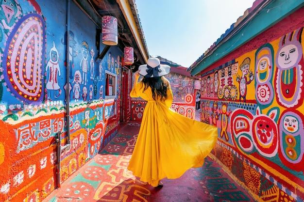 Frau, die am regenbogendorf in taichung, taiwan steht.