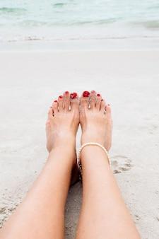 Frau, die am sandstrand spazieren geht und einen fußabdruck im sand hinterlässt schönheitsgesundheits-hautpflegekonzept