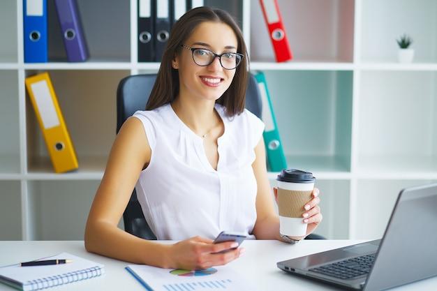 Frau, die am schreibtisch, arbeitend an laptop im modernen büro sitzt