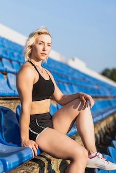 Frau, die am stadion betrachtet kamera sitzt