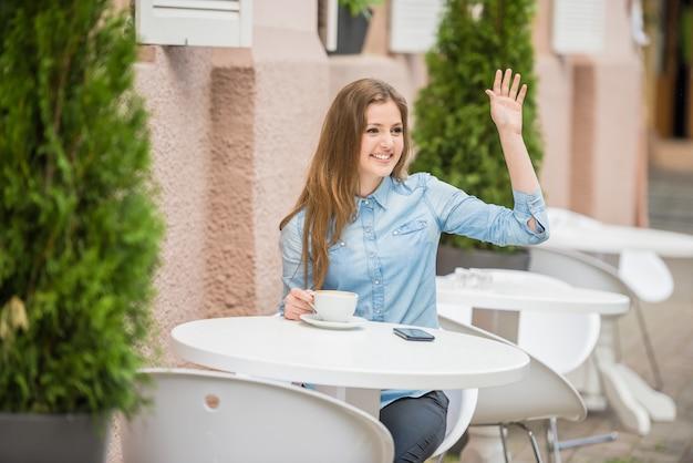 Frau, die am städtischen café im sommer sitzt und um kellner bittet.