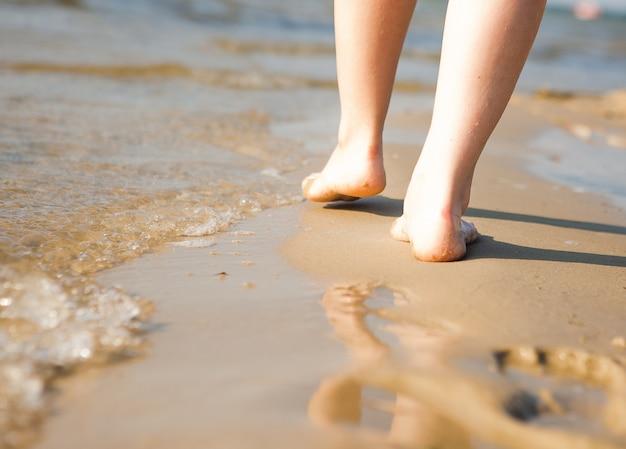 Frau, die am strand geht und einen fußabdruck im sand hinterlässt