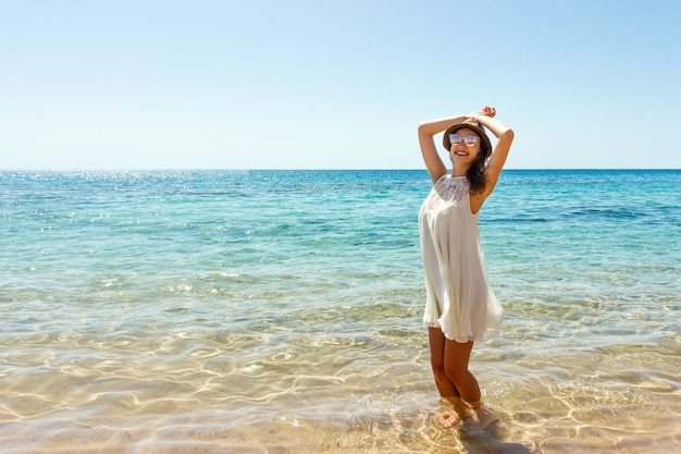 Frau, die am strand genießt sommerfreiheit sich entspannt. happ mädchen am strand