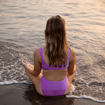 Frau, die am strand im badeanzug meditiert