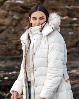 Frau, die am strand mit winterjacke aufwirft