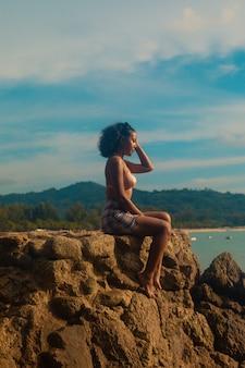 Frau, die am strand sitzt und den atemberaubenden sonnenaufgang genießt