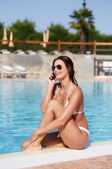 Frau, die am swimmingpool sich entspannt