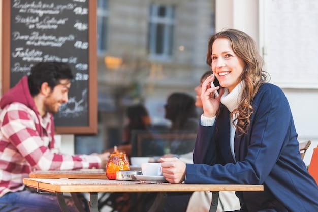 Frau, die am telefon an einem café spricht