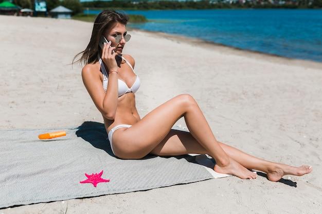 Frau, die am telefon auf strand spricht