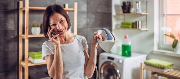 Frau, die am telefon beim bügeln von kleidung spricht