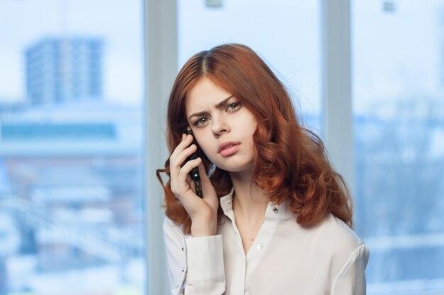 Frau, die am telefon gegen das fenster spricht