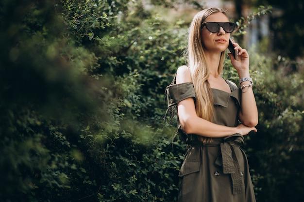 Frau, die am telefon im park spricht