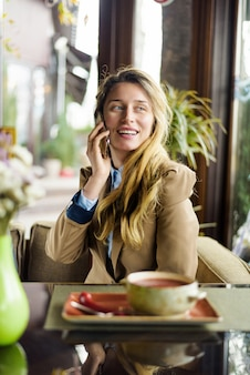 Frau, die am telefon im restaurant am business-lunch spricht