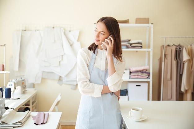 Frau, die am telefon in der werkstatt spricht