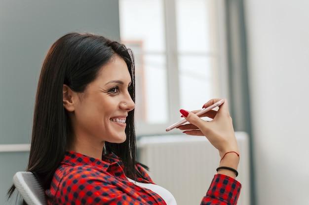Frau, die am telefon mit dem digitalen sprachassistenten spricht