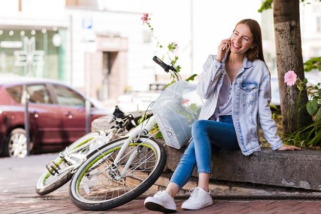 Frau, die am telefon nahe bei fahrrad spricht