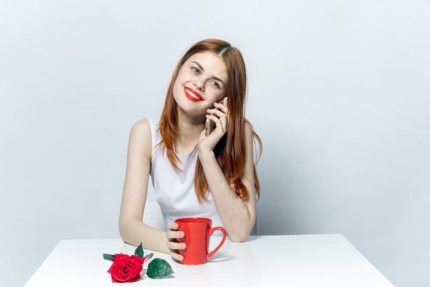 Frau, die am telefon spricht, das an der tischschale mit einem getränk rote rose sitzt