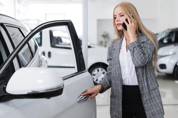 Frau, die am telefon spricht und autotür öffnet