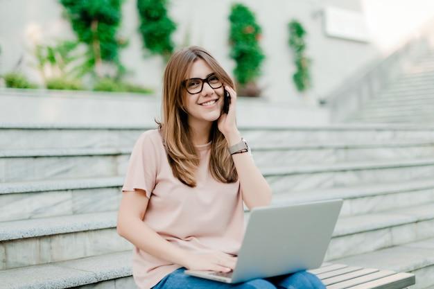 Frau, die am telefon spricht und draußen an laptop arbeitet
