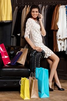 Frau, die am telefon spricht und im einkaufszentrum mit einkäufen sitzt