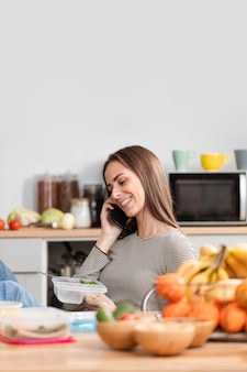 Frau, die am telefon spricht und isst