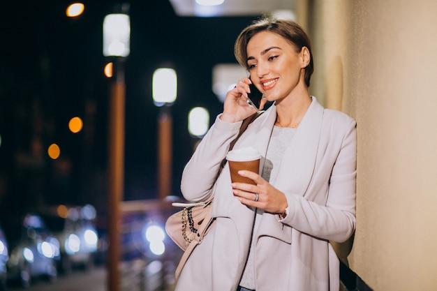 Frau, die am telefon spricht und kaffee draußen in der straße nachts trinkt