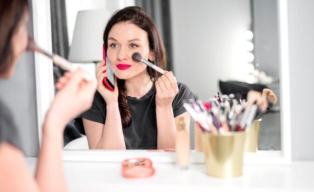 Frau, die am telefon spricht und make-up macht