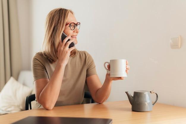 Frau, die am telefon spricht und während der quarantäne kaffee trinkt