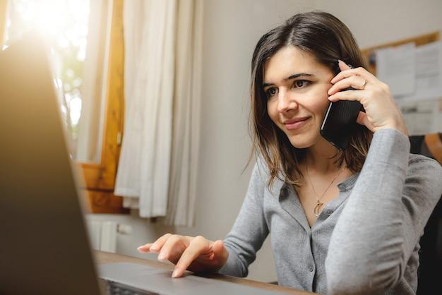 Frau, die am telefon spricht, während sie am computer im schreibtischbüro arbeitet. suche im internet