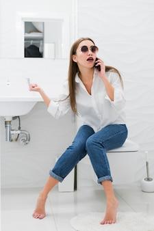 Frau, die am telefon spricht, während sie auf der toilette sitzt