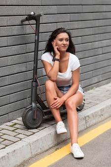 Frau, die am telefon spricht, während sie auf roller sitzt