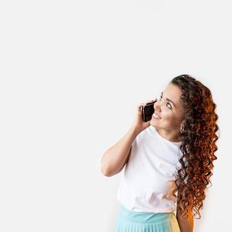 Frau, die am telefon spricht, während sie aufschaut