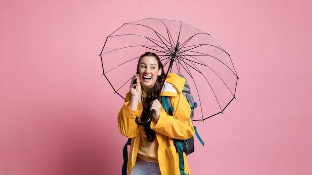 Frau, die am telefon spricht, während sie einen regenschirm hält