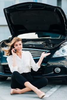 Frau, die am telefon und am schwarzen auto spricht