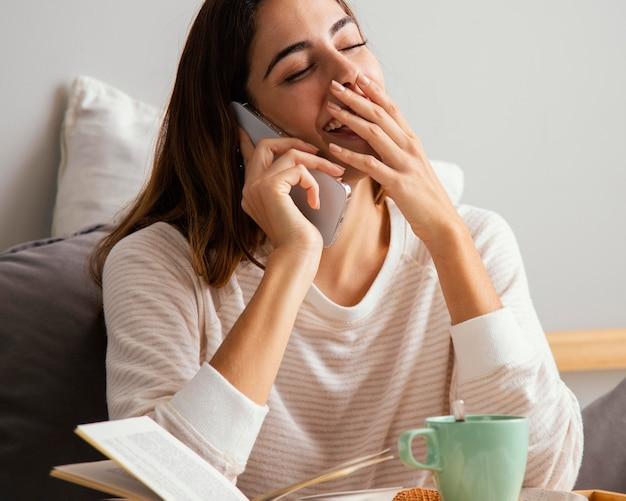 Frau, die am telefon und zu hause spricht und lacht
