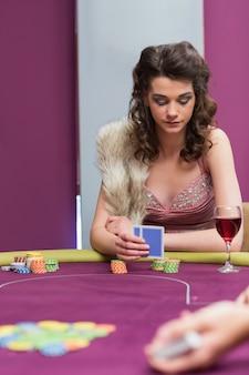 Frau, die am tisch betrachtet ihre chips im kasino sitzt