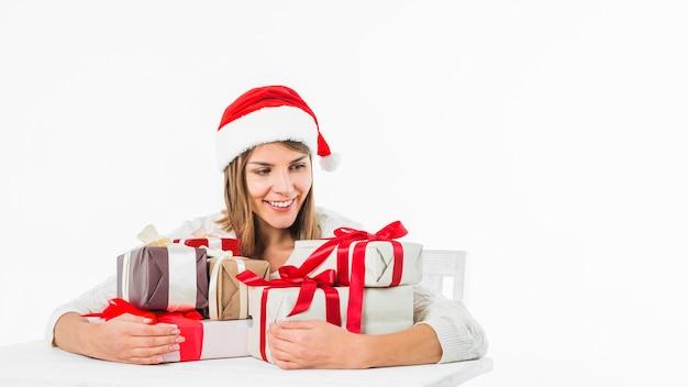 Frau, die am tisch mit geschenkboxen sitzt