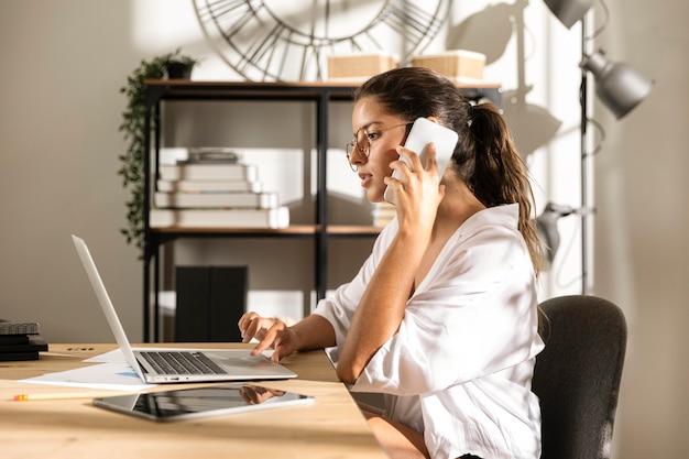 Frau, die am tisch sitzt und am telefon spricht