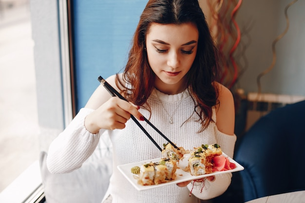 Frau, die am tisch sitzt und sushi im café isst