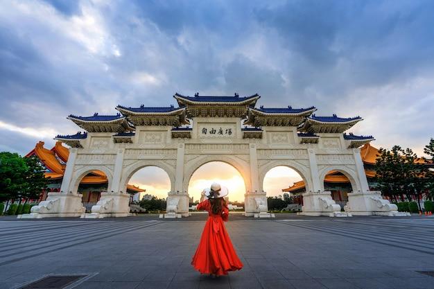 Frau, die am torbogen der chiang kai shek memorial hall in taipeh, taiwan geht.