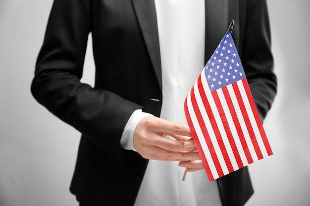 Frau, die amerikanische flagge auf licht hält. einwanderung in die usa