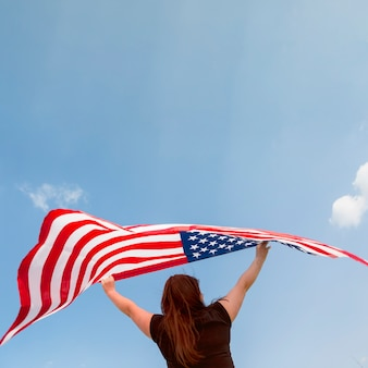 Frau, die amerikanische flagge hält
