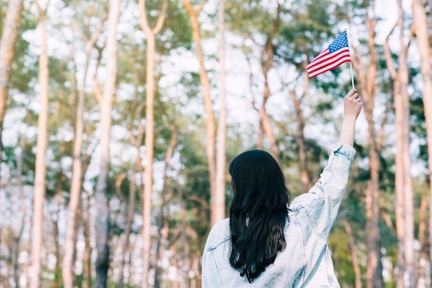 Frau, die amerikanische flagge wellenartig bewegt